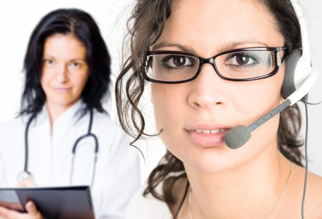 Triage Answering Service Operator wearing glasses and a headset stands in front of a triage nurse holding a clipboard and wearing a stethoscope.