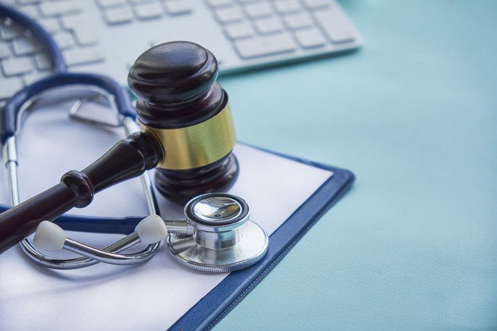 Gavel and stethoscope rest on a medical binder beside a computer keyboard.