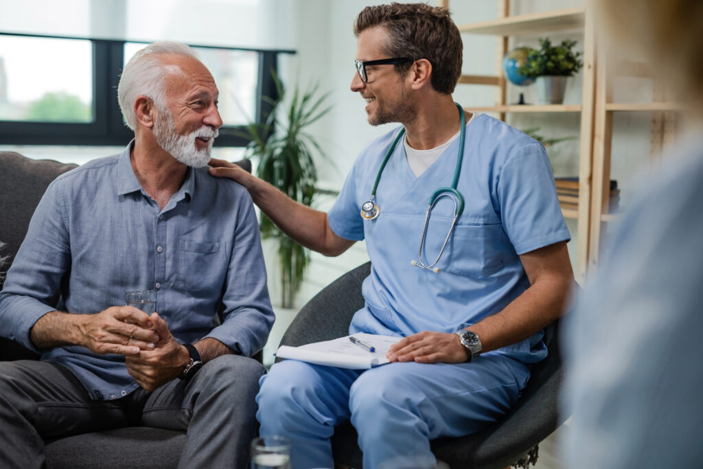 Happy doctor talks to senior male patient at home.